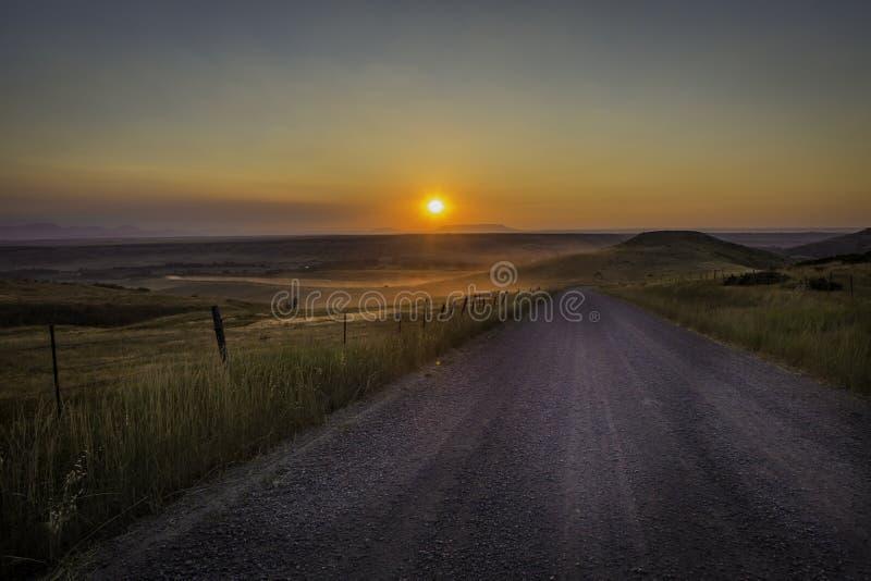 Por do sol empoeirado da estrada de terra em América rural foto de stock