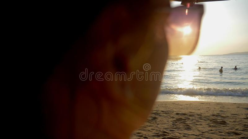 Por do sol ensolarado bonito no mar Vista através dos óculos de sol a mulher nos óculos de sol olha o por do sol no mar fotografia de stock royalty free