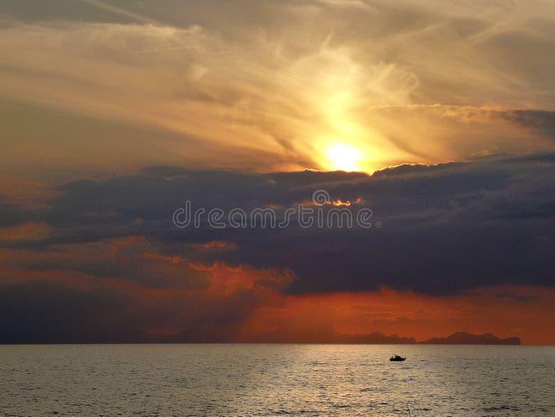 Por do sol espetacular com céu e as nuvens vermelhos sobre o mar de Menorca na Espanha com a silhueta de um barco na reflexão bri fotografia de stock
