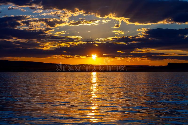 Por do sol espetacular com raios do deus no lago Powell foto de stock