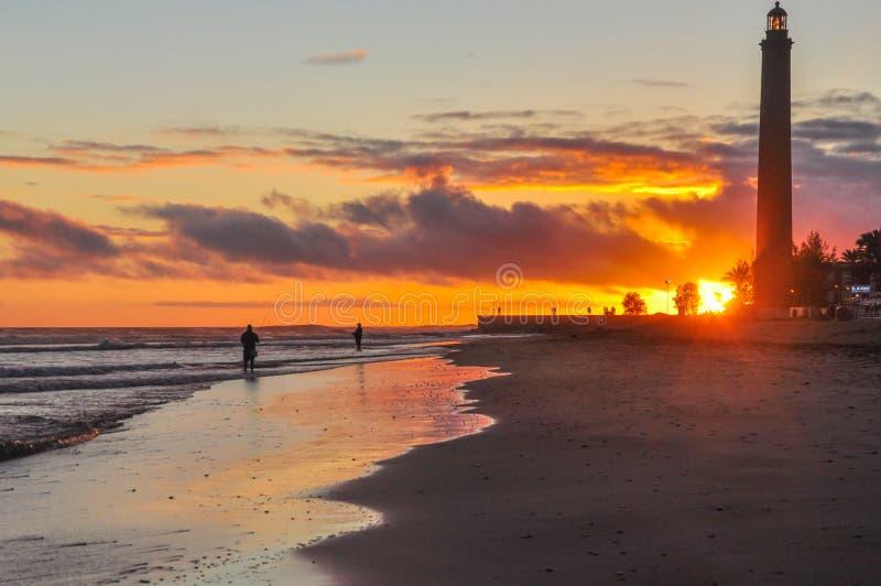 Por do sol espetacular na praia de Maspalomas no parque nacional e nas dunas de areia Pescadores e farol famoso no pico do sul de fotografia de stock