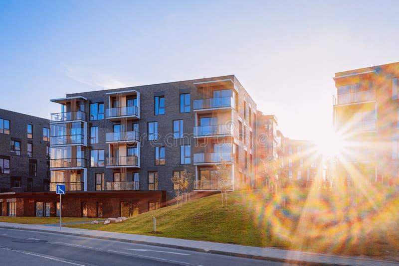 Por do sol exterior liso moderno dos bens imobiliários do prédio de apartamentos foto de stock