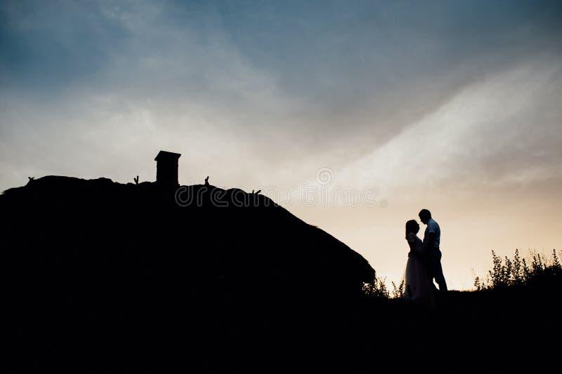 Por do sol feliz do céu da silhueta do feriado do amante dos pares imagem de stock