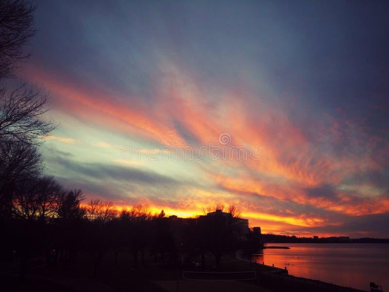 Por do sol do fogo sobre o lago frio foto de stock