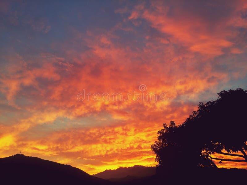 Por do sol do fogo sobre uma silhueta da montanha e de árvores tropicais fotografia de stock