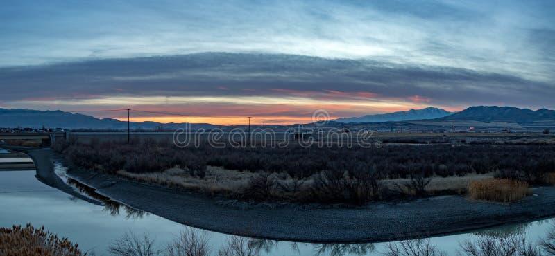 Por do sol impressionante além do rio e das montanhas fotografia de stock