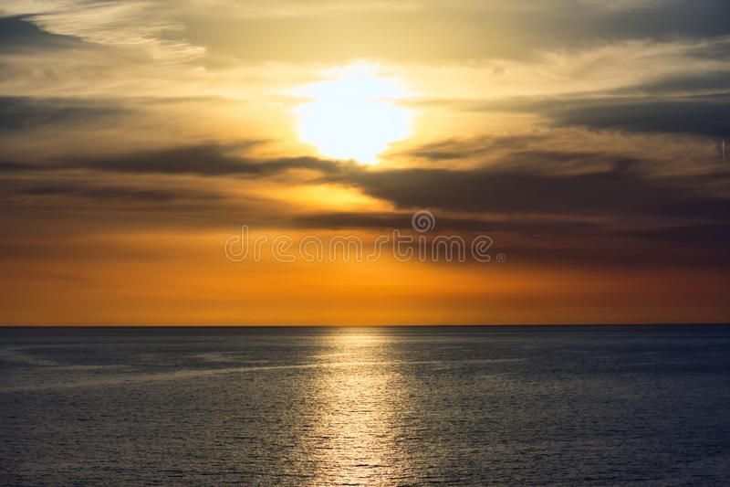 Por do sol impressionante em um céu dramático acima de um oceano sereno fotografia de stock royalty free