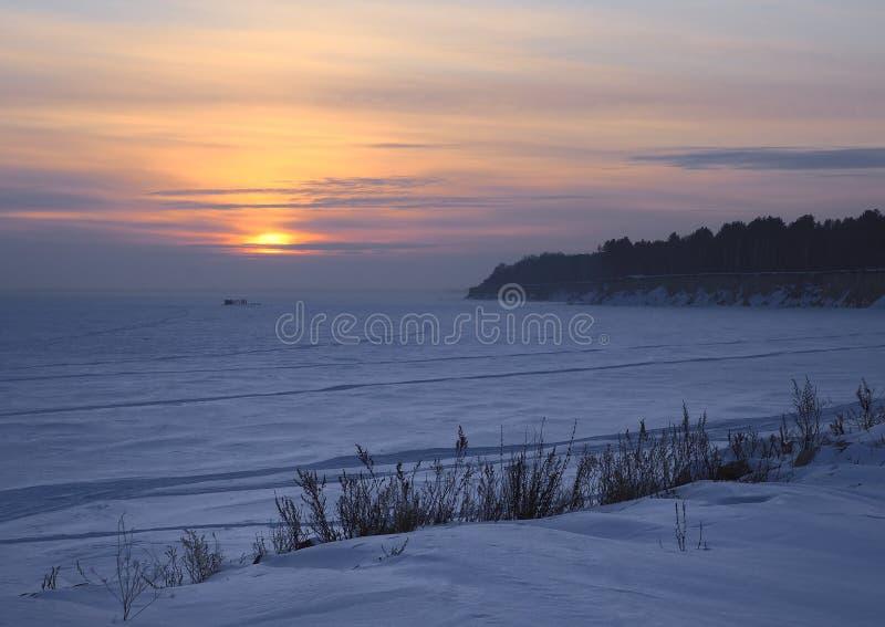 Por do sol do inverno no banco do reservatório congelado fotografia de stock royalty free