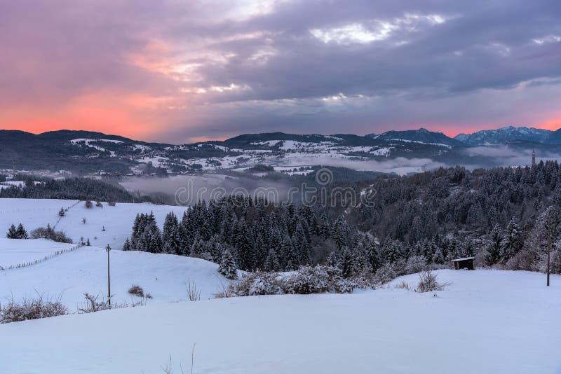 Por do sol do inverno sobre a paisagem nevado bonita da montanha nos cumes imagem de stock