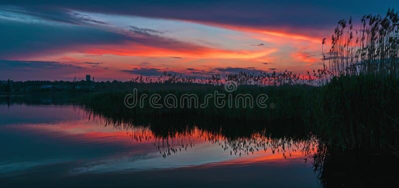 Por do sol lindo com as nuvens refletidas na água do lago fotografia de stock