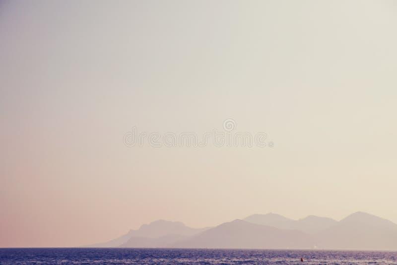Por do sol do mar Céu da baunilha, água contra montanhas na distância Abrandamento e férias do conceito fotografia de stock