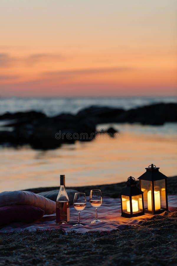 Por do sol do mar do verão Piquenique romântico na praia Garrafa do vinho, fotografia de stock
