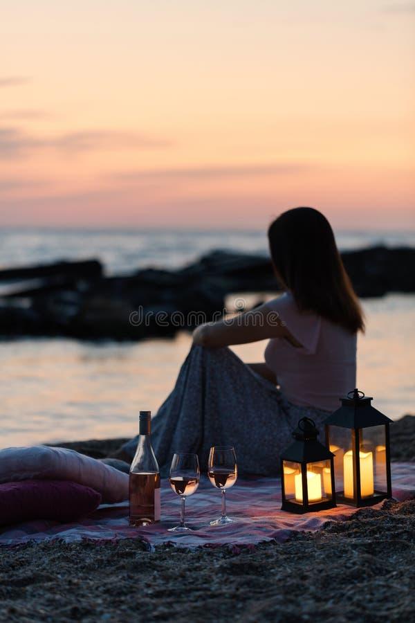 Por do sol do mar do verão Piquenique romântico na praia Garrafa do vinho, imagens de stock royalty free