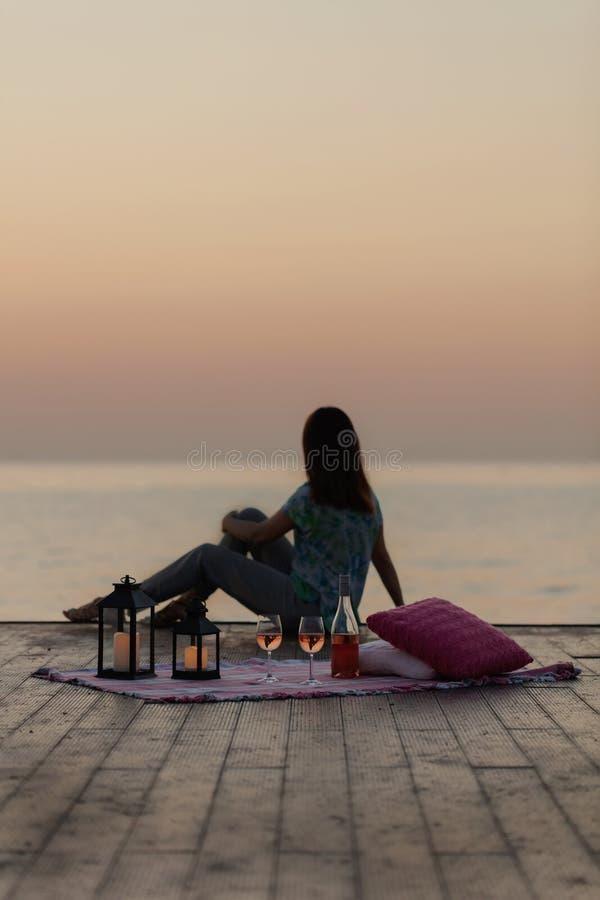 Por do sol do mar do verão Piquenique romântico na praia Garrafa do vinho, imagem de stock