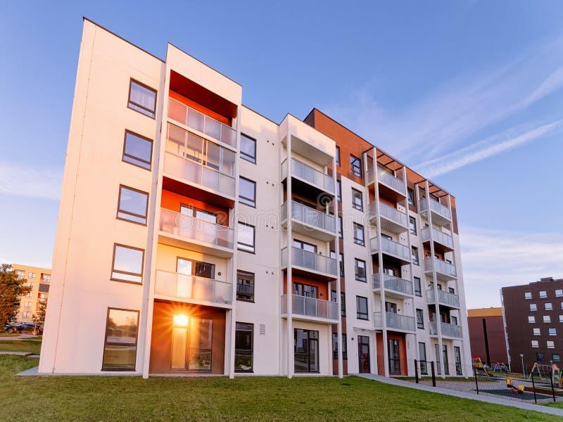 Por do sol moderno dos bens imobiliários de construção residencial da casa e da casa do apartamento imagem de stock