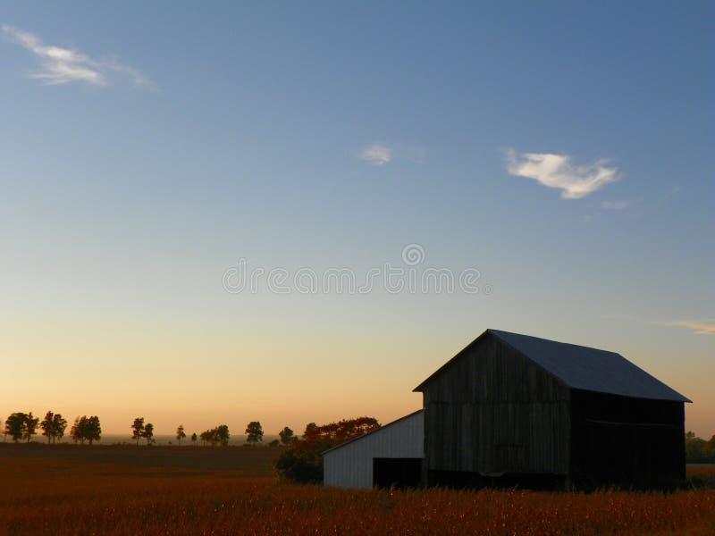 Por do sol morno da noite do outono com celeiro e fileds fotos de stock royalty free