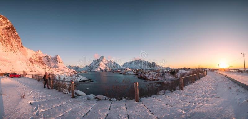 Por do sol na aldeia piscatória com a montanha nevado em Reine imagem de stock royalty free