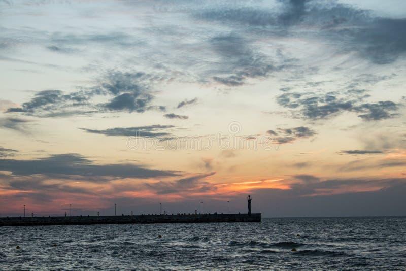 Por do sol na costa de mar, foto de stock