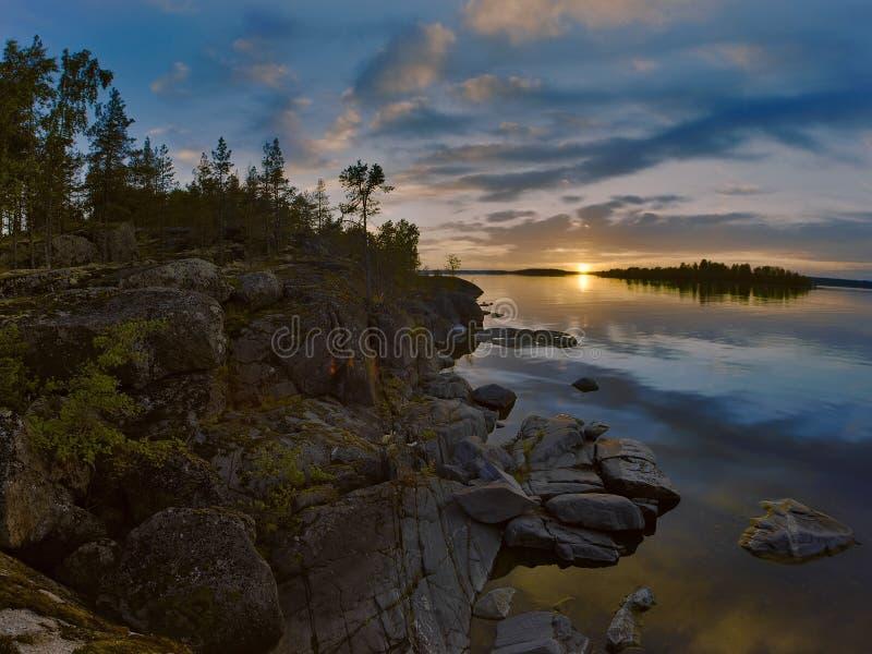Por do sol na costa rochoso do lago ladoga imagens de stock