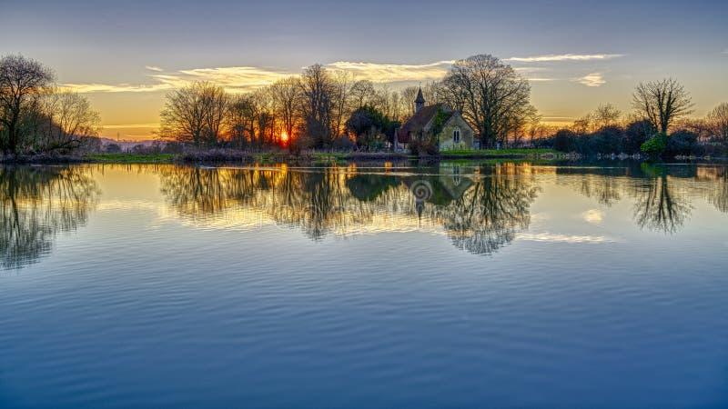 Por do sol na lagoa de Hartley Mauditt para a igreja de St Leonard, penas sul parque nacional, Hampshire, Reino Unido fotos de stock royalty free