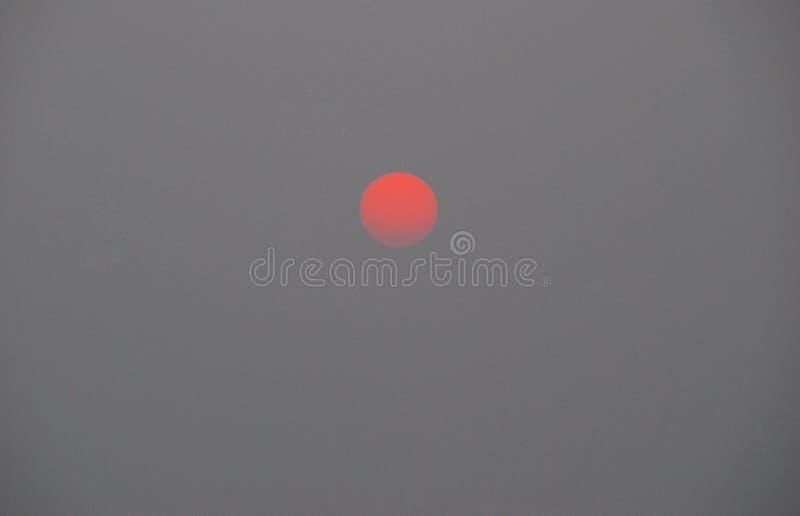 Por do sol na poluição pesada, poluição atmosférica, sol, céu, céu sob a poluição do ar, céu cinzento da cidade foto de stock