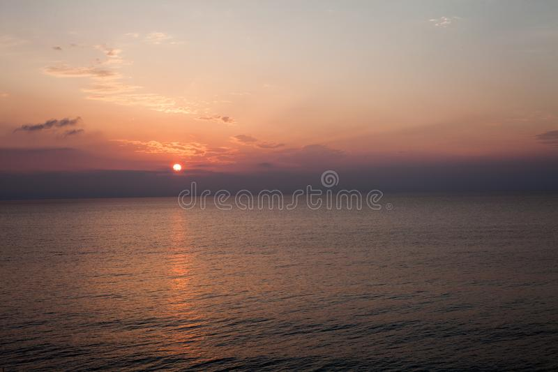 Por do sol na praia com algumas nuvens no céu Máscaras azuis e cor-de-rosa com nuvens escuras Lugar quieto Cena de relaxamento da imagens de stock