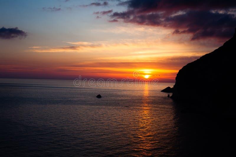 Por do sol na praia com montanhas e nuvens Água do mar calma Cores bonitas no céu Máscaras azuis e alaranjadas Lugar quieto r fotografia de stock royalty free