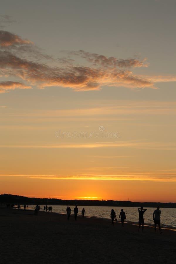 Por do sol na praia com nuvens alaranjadas fotografia de stock royalty free