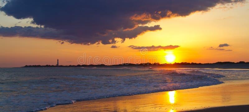Por do sol na praia com um farol fotografia de stock