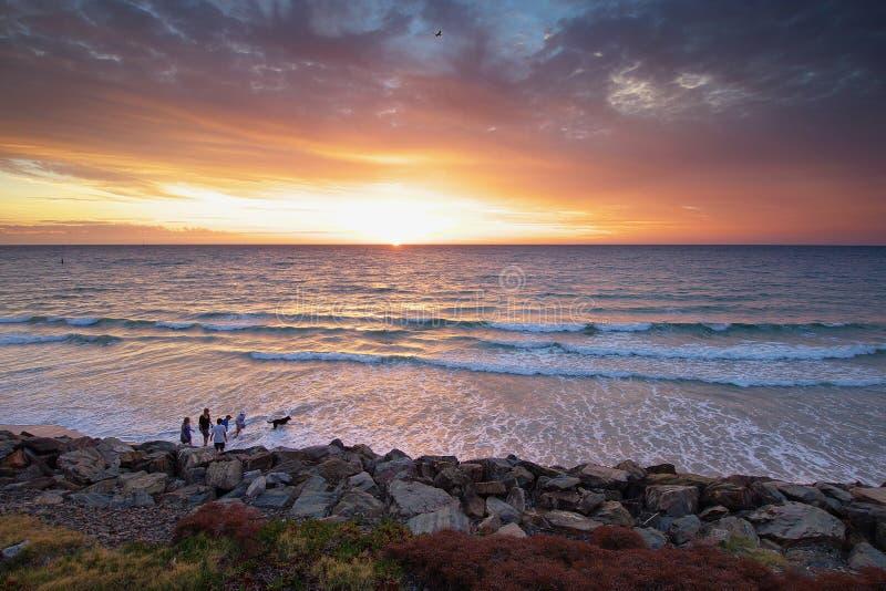 Por do sol na praia com um passeio da família imagem de stock
