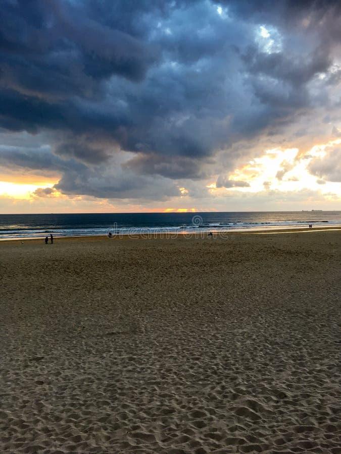 Por do sol na praia de Carcavelos em Portugal imagens de stock