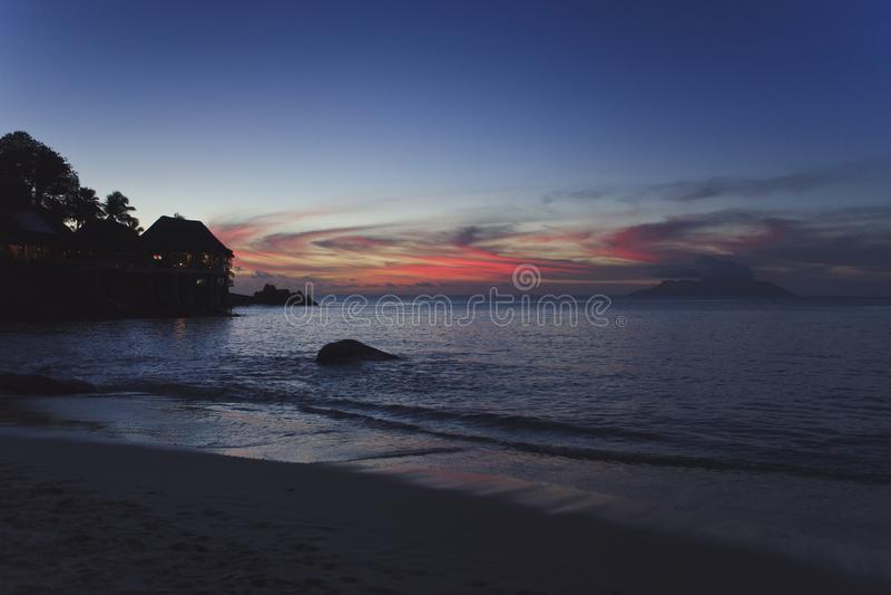 Por do sol na praia de uma ilha tropical Na costa de algumas casas de ilha pequenas foto de stock royalty free