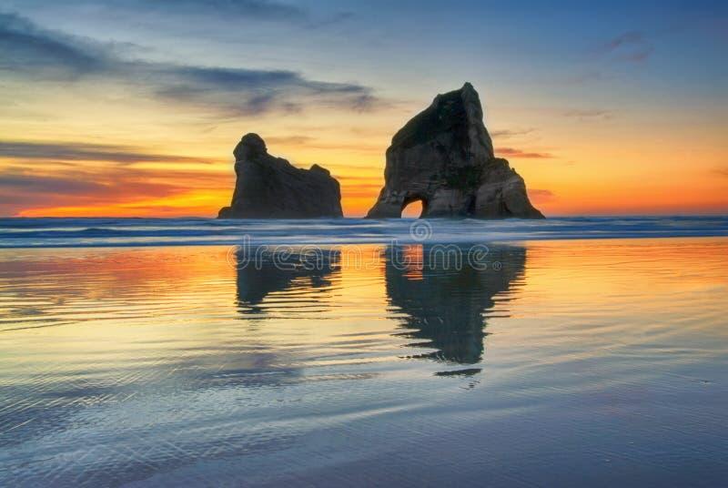 Por do sol na praia de Wharariki, Nova Zelândia foto de stock royalty free