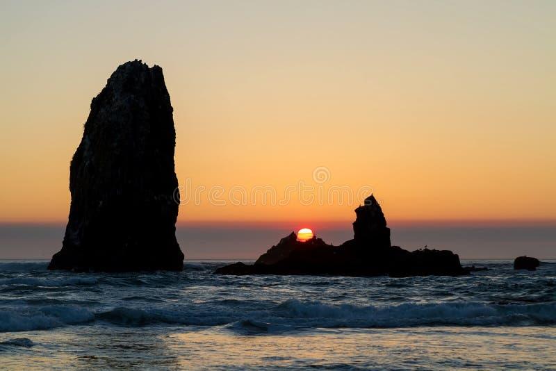 Por do sol na praia do canhão ao longo da costa de Oregon imagem de stock