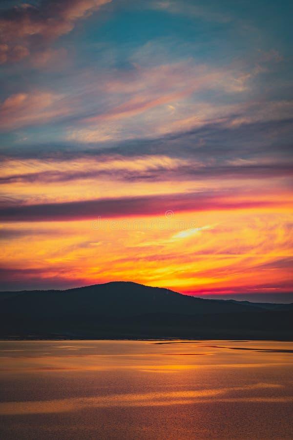 Por do sol nebuloso ardente bonito no lago com o sol ido atrás das montanhas fotografia de stock