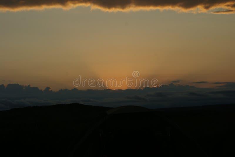 Por do sol nebuloso com um fulgor dourado fotografia de stock