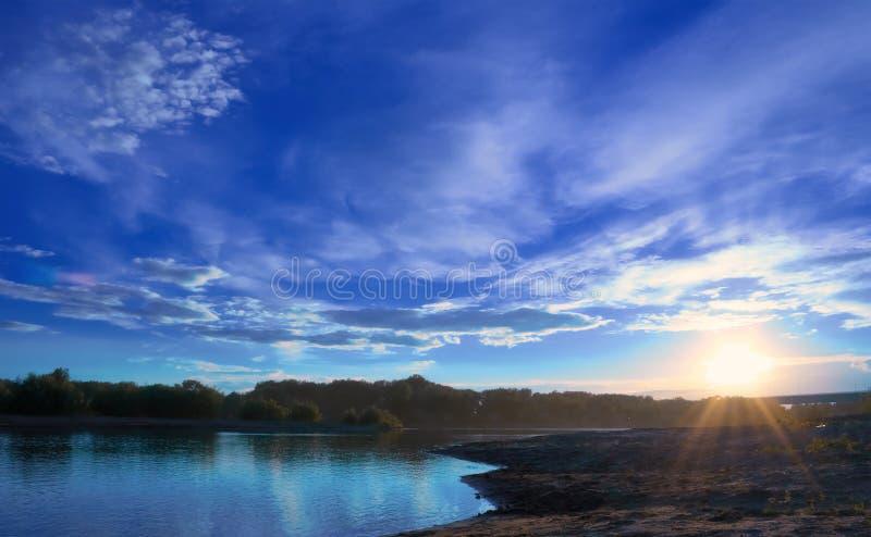 Por do sol no banco do rio foto de stock royalty free