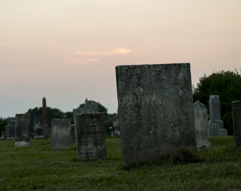 Por do sol no cemitério com lápide foto de stock royalty free