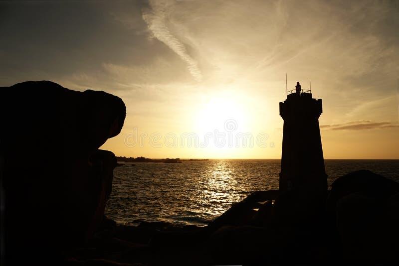 Por do sol no farol do ruz dos homens na costa cor-de-rosa do granito em Brittany fotos de stock royalty free