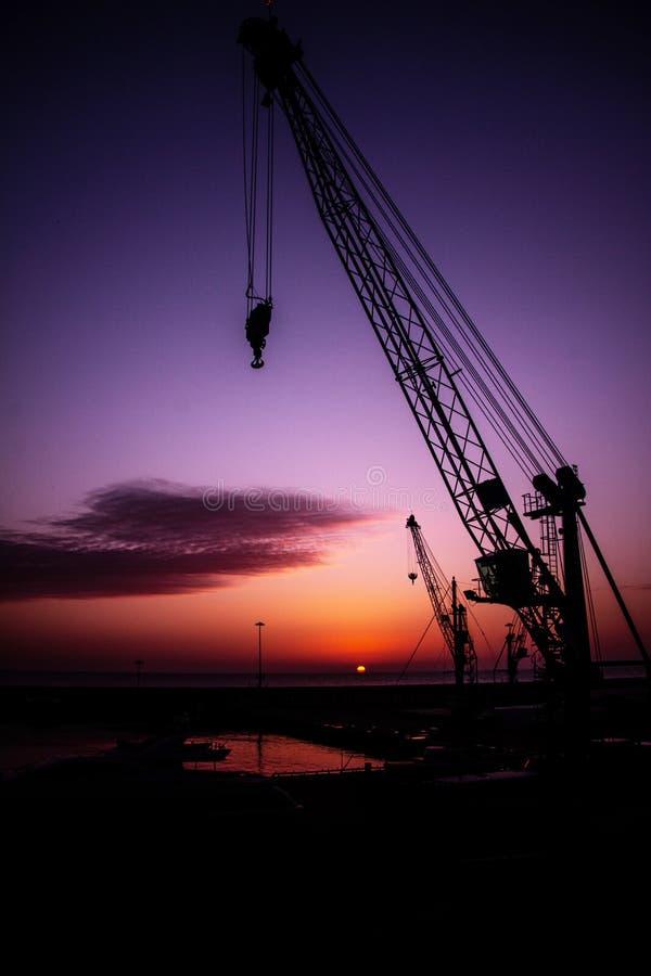 Por do sol no fundo de guindastes de construção no mar fotos de stock royalty free