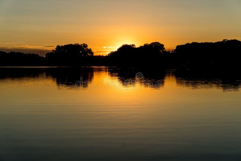 Por do sol no lago cinzento do ` s imagem de stock