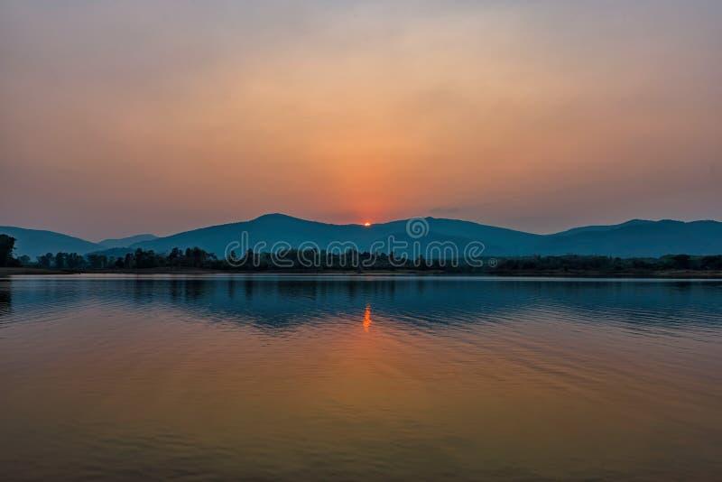 Por do sol no lago da montanha em Chiang Rai, ao norte de Tailândia foto de stock