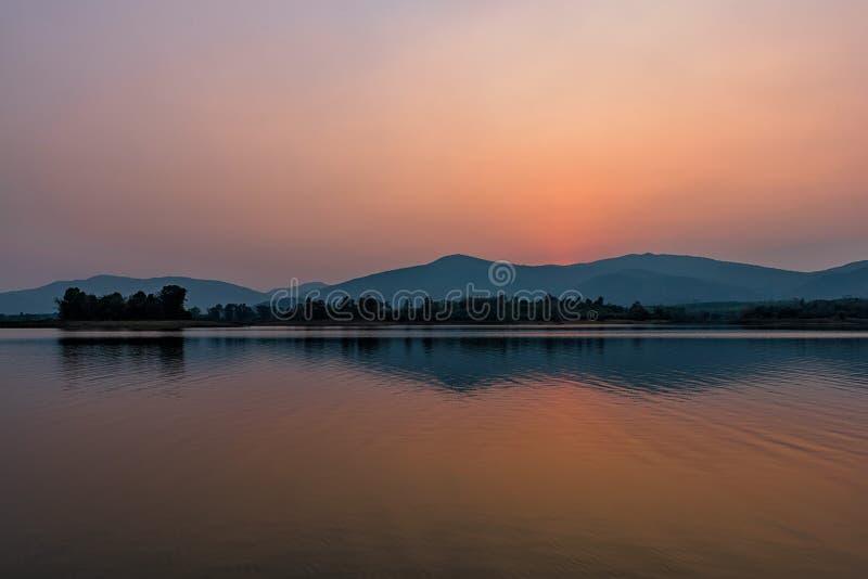 Por do sol no lago da montanha em Chiang Rai, ao norte de Tailândia foto de stock royalty free