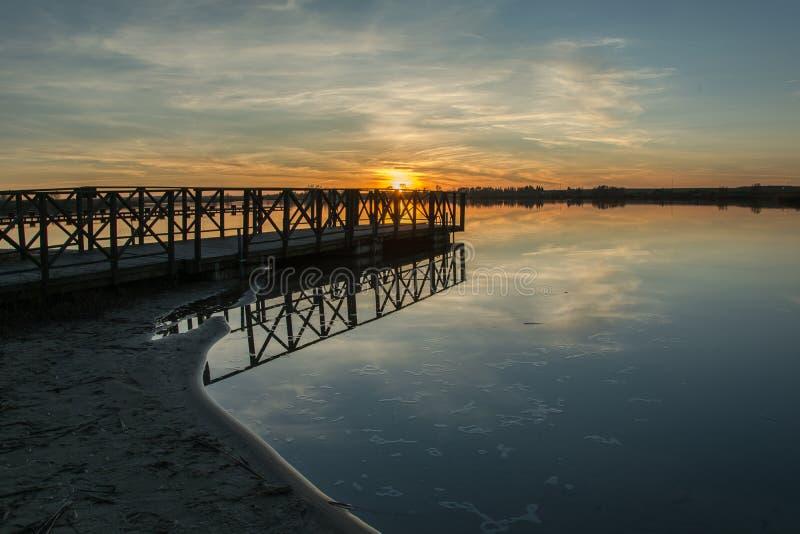 Por do sol no lago, molhe de madeira na costa arenosa foto de stock