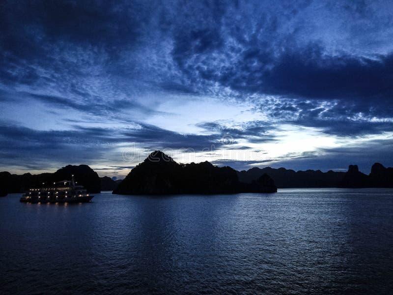 Por do sol no louro de Halong Com o um navio iluminado no fundo e no céu azul do tom e o dramático fotos de stock royalty free