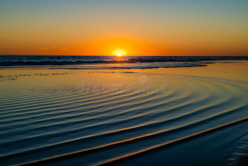 Por do sol no mar com as ondas circulares na água fotos de stock royalty free