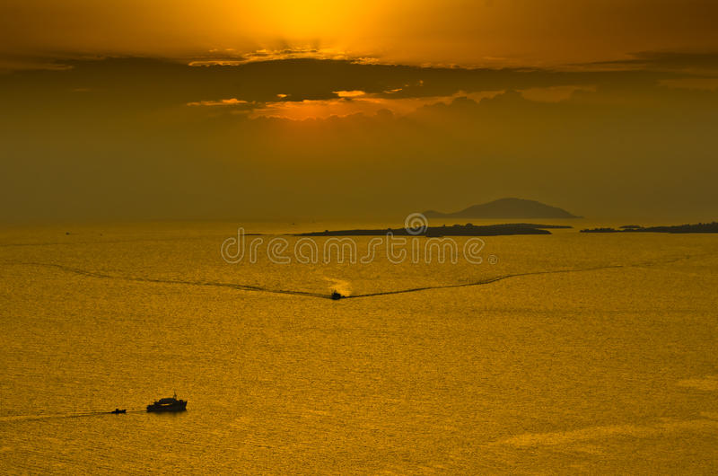 Por do sol no mar, com barco de pesca e redes entre ilhas pequenas, Sithonia fotos de stock royalty free