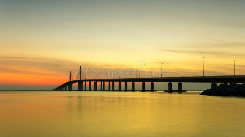 Por do sol no mar com a ponte sobre o panorama calmo da água foto de stock royalty free
