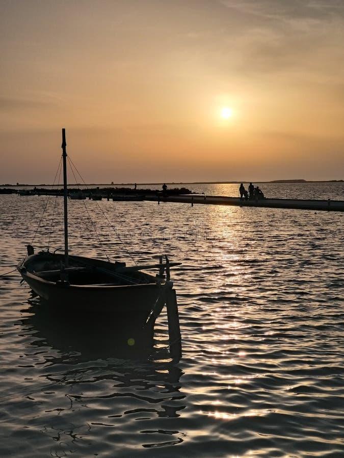Por do sol no mar e no barco foto de stock royalty free
