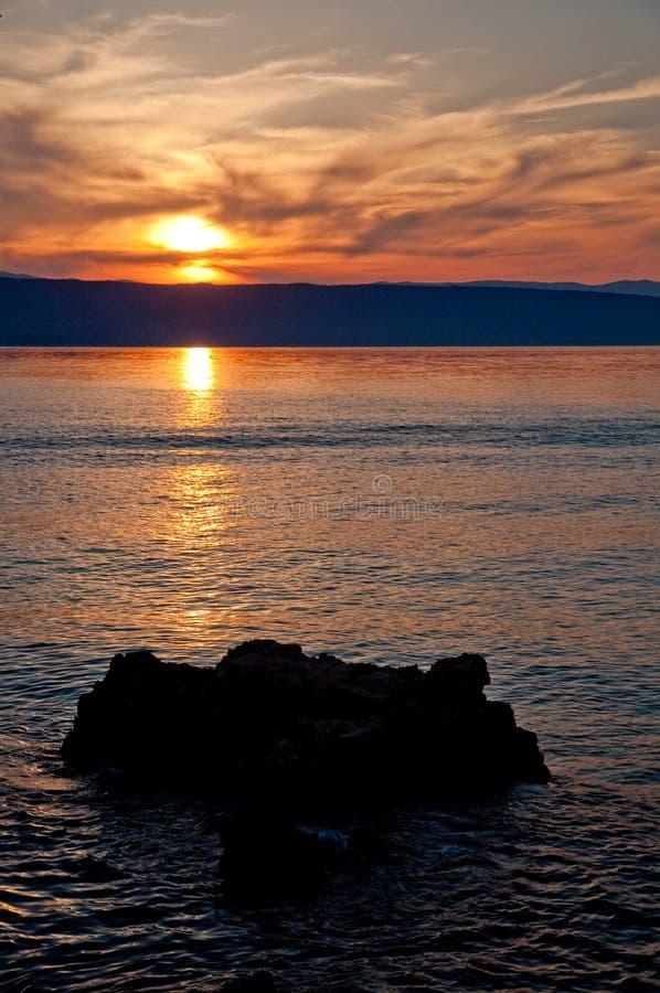 Por do sol no mar em Glavotok com pedra - Croatia - Krk fotos de stock royalty free